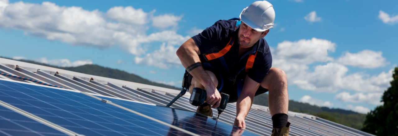solar installer on the roof of a solar energy system