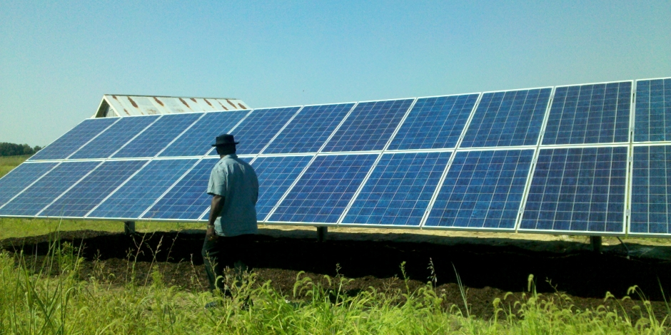 man in front of ground mounted solar panels
